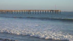 Ventura, California Pier View y personas que practica surf que se baten hacia fuera durante la última hora de la tarde almacen de metraje de vídeo