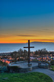 Ventura hillside cross silhouetted against sunset glow. Royalty Free Stock Photography