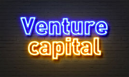 Venture capital neon sign on brick wall background. Stock Image