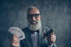 Venturesome, uprawiający hazard, ono uśmiecha się, szczęsliwy stary milioner w szkłach zdjęcie stock
