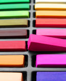 Venturing out of box. A concept image for out of the box ideas.  Colorful artists pastel sticks lined neatly in a box except for one bright pink one half taken Royalty Free Stock Photo