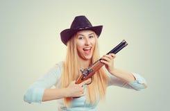 Woman in cowboy hat holding gun stock photos