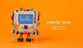 Venuta in costruzione del sito Web presto pagina del modello Robot del giocattolo con la chiave e le pinze della mano Fondo aranc fotografia stock libera da diritti
