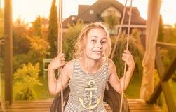 verão - criança feliz da menina da criança no jardim no balanço Imagem de Stock