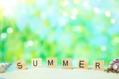 verão da inscrição na areia com escudos em um fundo brilhante do verão com luz do sol fotos de stock royalty free
