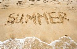 verão escrito à mão na areia molhada no litoral Fotos de Stock