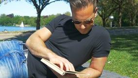 verão na cidade - um homem relaxa no gramado no parque e lê um livro vídeos de arquivo