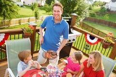 verão: O paizinho serve acima Hamburger e cachorros quentes Fotografia de Stock