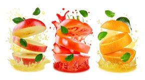 Veränderung des Fliegens schnitt Apple, Orange und Tomate mit Saft s Stockbilder