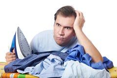 Verärgern Sie Mann mit Stapel der Wäscherei, bevor Sie lokalisiert bügeln lizenzfreies stockfoto