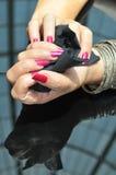 Verärgern Sie weibliche Hände mit den roten Nägeln, die schwarzes Papiergewebe einwickeln Stockbilder