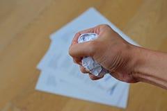 Verärgert bei der Arbeit mit dem Handzerknitternden Papier, das in eine Faust mit Dokumenten im Hintergrund sich bildet Stockfotografie