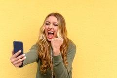 Verärgerte blonde Frau, die an ihrem Handy schreit Lizenzfreie Stockfotografie