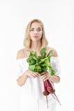 Verärgerte blonde Frau hält Rote-Bete-Wurzeln mit grünen Blättern auf weißem Hintergrund Gesundheit und Vitamine Lizenzfreies Stockbild
