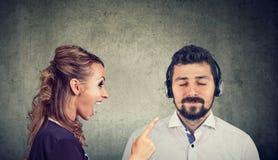 Verärgerte Frau, die an einem ruhigen Ehemann hört Musik schreit stockfoto