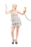 Verärgerte Frau, die einen Telefonsprecher hält Stockfotos