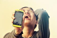 Verärgerte Frau, die gebrochenen Smartphone hält Stockfoto