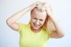 Verärgerte Frau, die ihr Haar in der Frustration zerreißt stockfoto