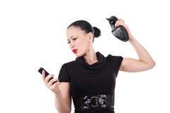 Verärgerte Frau, die ihr smartphone mit ihrem Schuh zertrümmert Lizenzfreies Stockfoto