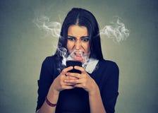 Verärgerte Frau, die an ihrem Handy, erzürnt mit schlechtem Service schreit lizenzfreies stockfoto