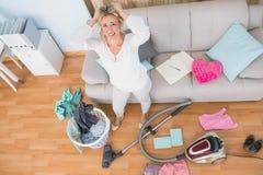 Verärgerte Frau in einem chaotischen Wohnzimmer mit Staubsauger stockfotos