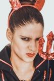 Verärgerte Frau im Teufelkarnevalskostüm Stockbilder