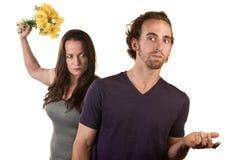 Verärgerte Frau mit Blumen und naivem Mann Stockfoto