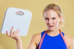 Verärgerte Frau mit Skala, Gewichtsverlustzeit für das Abnehmen Lizenzfreie Stockfotografie