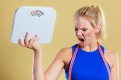 Verärgerte Frau mit Skala, Gewichtsverlustzeit für das Abnehmen Stockbilder
