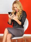 Verärgerte frustrierte Geschäftsfrau, die ein Mobiltelefon verwendet Lizenzfreie Stockfotografie