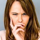 Verärgerte frustrierte junge Frau, die im Widerspruch die Stirn runzelt stockfotos