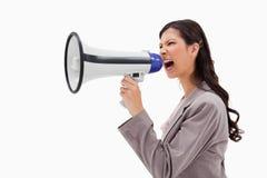 Verärgerte Geschäftsfrau, die durch Megaphon schreit Stockbild