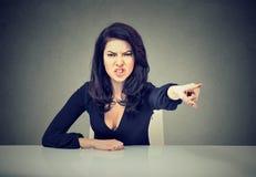 Verärgerte Geschäftsfrau, die an ihrem Schreibtisch und an schreienden Zeigen mit dem Finger zum hinauszugehen sitzt Stockfotos