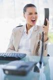Verärgerte Geschäftsfrau, die an ihrem Telefon schreit Stockfoto