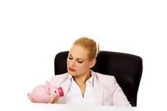 Verärgerte Geschäftsfrau, die nach ihrem piggybank sucht und hinter dem Schreibtisch sitzt Lizenzfreies Stockfoto
