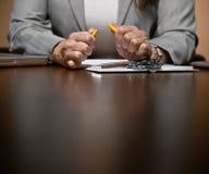 Verärgerte Geschäftsfrau, die spät am Schreibtisch arbeitet Stockbilder