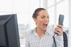 Verärgerte Geschäftsfrau, die am Telefon schreit Lizenzfreies Stockfoto