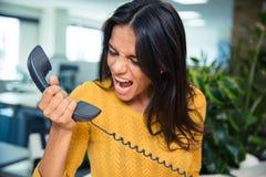 Verärgerte Geschäftsfrau, die am Telefon schreit Stockbild
