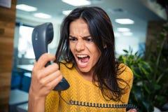 Verärgerte Geschäftsfrau, die am Telefon schreit Lizenzfreies Stockbild