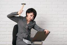 Verärgerte Geschäftsfrau mit Laptop und die Ordner, die Druck, kleiden lassen in einer grauen Klage, wirft vor einer weißen Wand  Lizenzfreie Stockfotografie