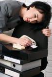 Verärgerte Geschäftsfrau mit Laptop und die Ordner, die Druck, kleiden lassen in einer grauen Klage, wirft vor einer weißen Wand  Stockfotografie