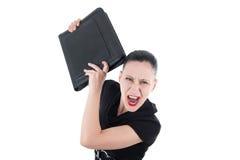 Verärgerte Geschäftsfrau mit ledernem Aktenkoffer Stockfotos