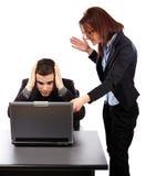 Verärgerte Geschäftsfrau, welche ihrem emplyee die Fehler auf einem Laptop zeigt Stockfoto