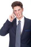 Verärgerte junge Exekutive, die Mobiltelefon verwendet Stockfoto