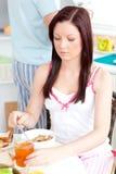 Verärgerte junge Frau, die in der Küche frühstückt Lizenzfreies Stockbild