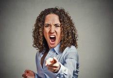 Verärgerte junge Frau, die Finger auf die schreiende Kamera zeigt Lizenzfreie Stockbilder