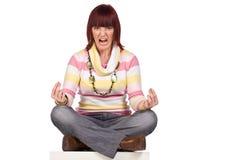 Verärgerte junge Frau, die mit überkreuzten Beinen, getrennt sitzt Lizenzfreies Stockfoto