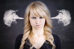 Verärgerte junge Frau, Schlagdampf, der aus Ohren herauskommt stockbild