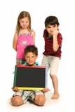 Verärgerte Jungen und Mädchen mit Tafel Stockfotos