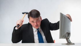 Verärgerte Männer, die Hammer über PC-Monitor halten Lizenzfreie Stockfotos